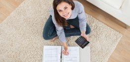 Woman Calculating Home Finances On Rug